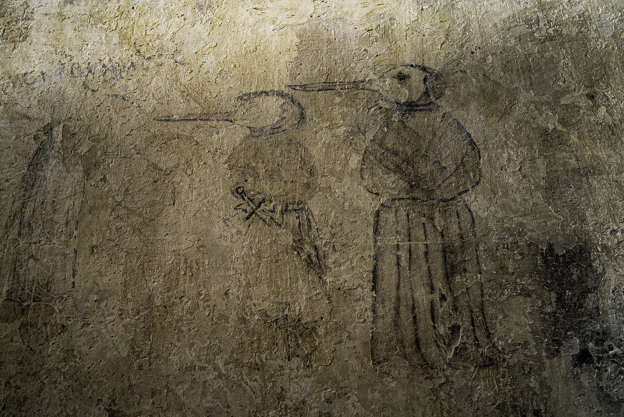 Physicians in black robes and bird beaked masks offered herbs and quarantine against the Black Plague